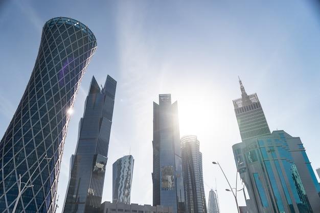 Современный центр города с башнями и небоскребами на фоне солнечного неба. доха, катар 2020.