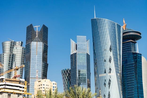 Современный центр города с башнями и небоскребами на солнечном небе