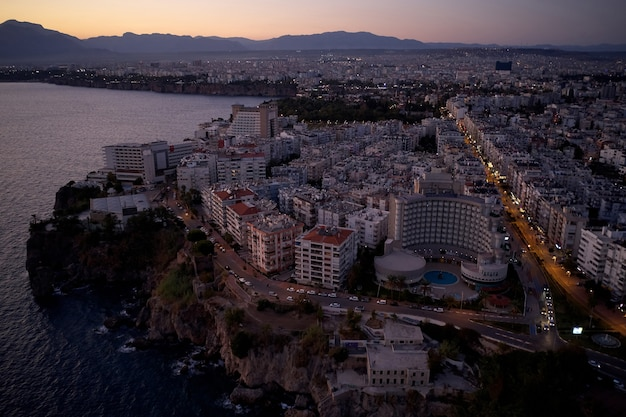 近代的な都市のスカイライン、トルコ、ヨーロッパ。日没時にホテルやアパートの建物とリゾートタウンの空中パノラマビュー。