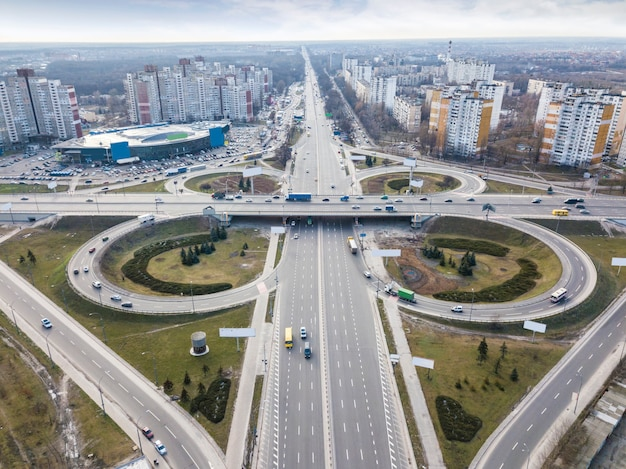 Modern city with the road in the form of a quatrefoil on the road junction of odessa square around background of a cloudy sky autumn day. aerial view from the drone. kiev, ukraine
