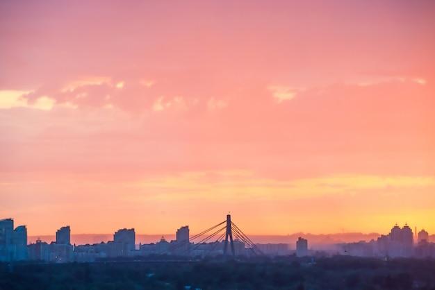 美しいカラフルな夕日を背景に橋と高層ビルのあるモダンな街並み