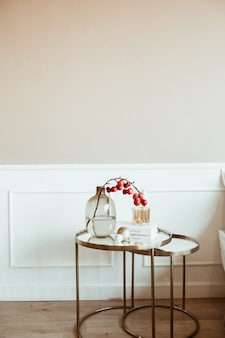 Modern classic interior design. decorated living room. bedside table with red berries bouquet in glass vase, book, candle in front of beige wall