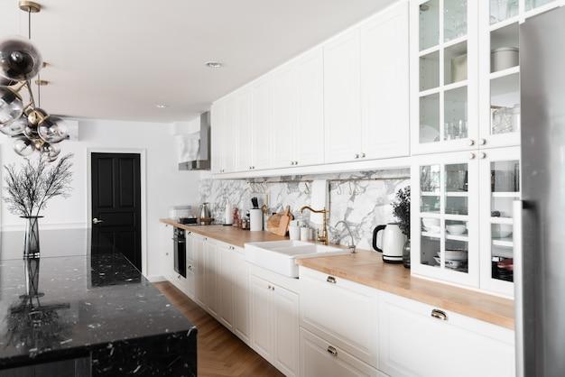 Современный классический кухонный интерьер с кухонной техникой и белой керамической раковиной с золотым зеркальным смесителем на деревянной поверхности с мраморной стеной