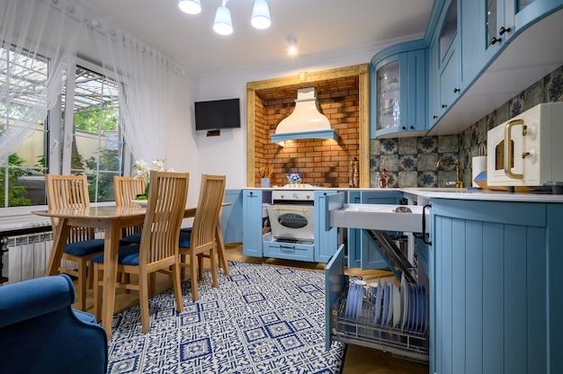 Современная классическая роскошная кухня и столовая с выдвижными ящиками и дверцами.