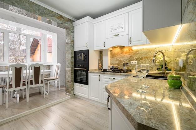 Современный классический интерьер белой кухни с обеденной зоной