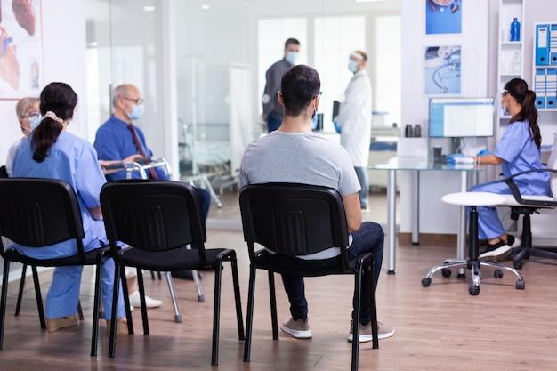コロナウイルスに対する安全対策としてフェイスマスクを着用している患者がいる現代の診療所の受付と待合室