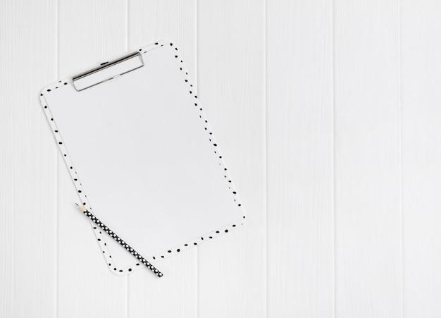 빈 시트와 흰색 나무 테이블에 연필 현대 클립 보드.