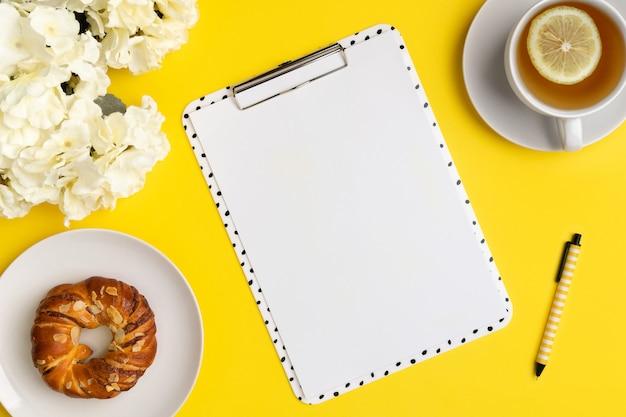 花とコーヒーと黄色の背景に空白のシートとモダンなクリップボード。フラットレイ、トップビューオフィスワーク教育の概念。