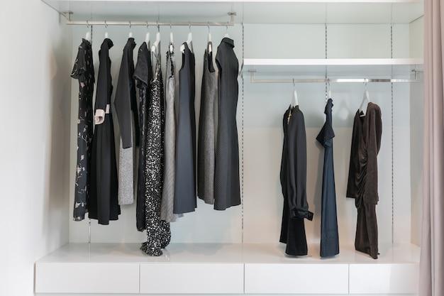 ワードローブのコートハンガーにぶら下がっている黒いドレスの列を備えたモダンなクローゼット。