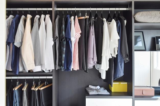 검은 옷장에 매달려 옷의 행과 현대 옷장