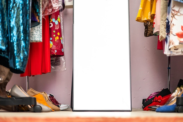 세련된 의류와 신발로 가득 찬 현대적인 옷걸이 클로우즈업 의류 및 액세서리 보관함