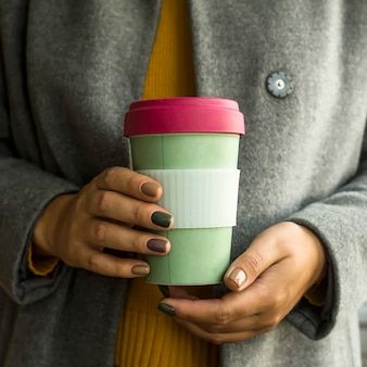 Modern coffee cup in the concept of zero waste in a woman's hands