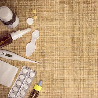 현대 감기 의학. 감기와 독감의 치료. 아픈 날과 독감 개념입니다. 다양한 의약품, 온도계, 갈색 배경에 코 막힌 스프레이. 공간을 복사합니다.