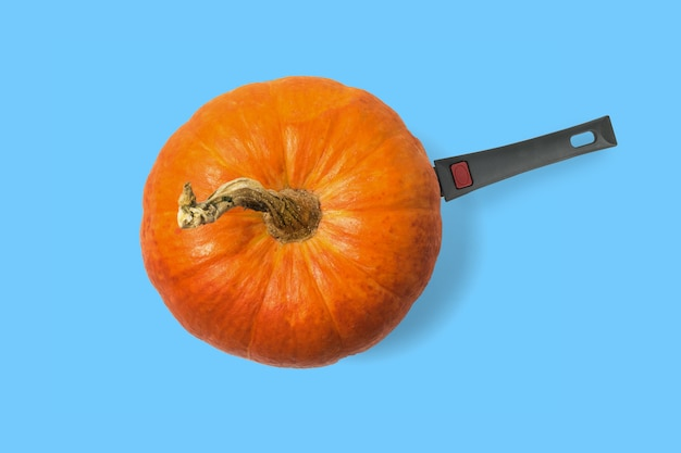 A modern collage of pumpkin with a frying pan handle on a blue background. a popular autumn vegetable.