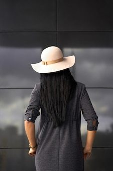 Modern collection. brunette girl wearing stylish grey dress and fashionable hat. model in trendy outfit posing on grey wall background. view from back.