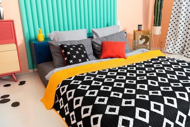 Современная красочная хипстерская необычная спальня с черно-белым текстилем и яркими акцентами.