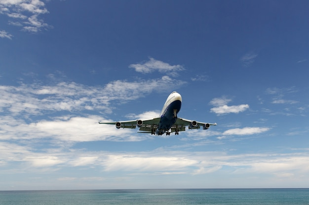 Modern commercial airplane jetliner flying in blue sky above the sea