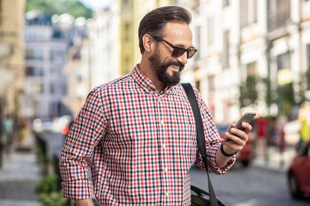 現代のコミュニケーション。散歩を楽しみながらスマートフォンを使って前向きなハンサムな男性の腰を上げる