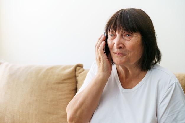 現代のコミュニケーションは、家庭で携帯電話で話しているカジュアルな服を着た白人の年配の女性を笑っています...