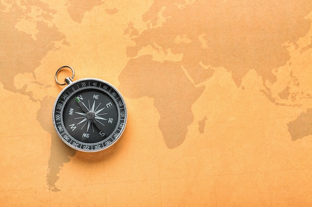 Современный компас на старинной карте мира. концепция планирования путешествия