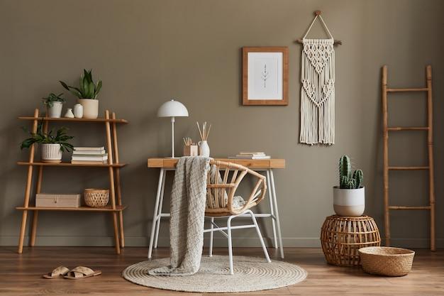 Современная композиция в интерьере домашнего офиса в стиле бохо с деревянным столом, стильным креслом, бамбуковой полкой, ковром, макраме, рамой, канцелярскими принадлежностями, украшениями и личными аксессуарами.