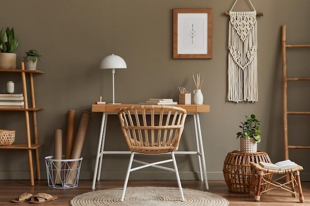 木製の机、スタイリッシュなアームチェア、竹の棚、カーペット、マクラメ、ポスターフレーム、事務用品、装飾品、身の回り品を備えたホームオフィスルームの自由奔放に生きるインテリアのモダンな構成。