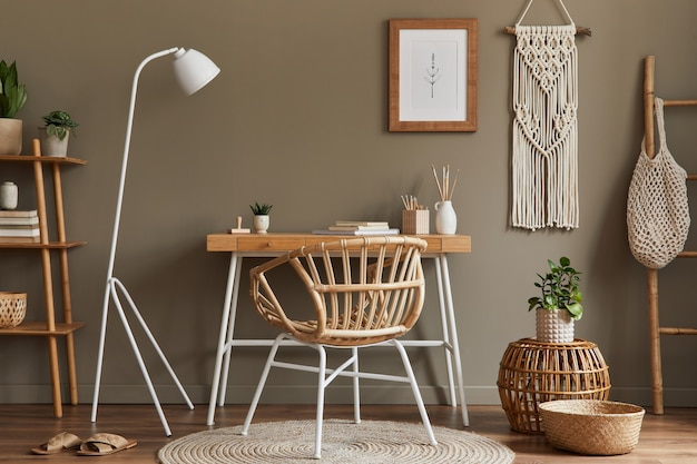 Modern composition at boho interior of home office room with wooden desk, stylish armchair, bamboo shelf, carpet, macrame, frame, office supplies, decoration and personal accessories.