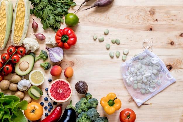 台所の木のテーブルに新鮮で健康的な野菜と果物の現代的な構成。健康的なデトックスとバランスの取れた食事。