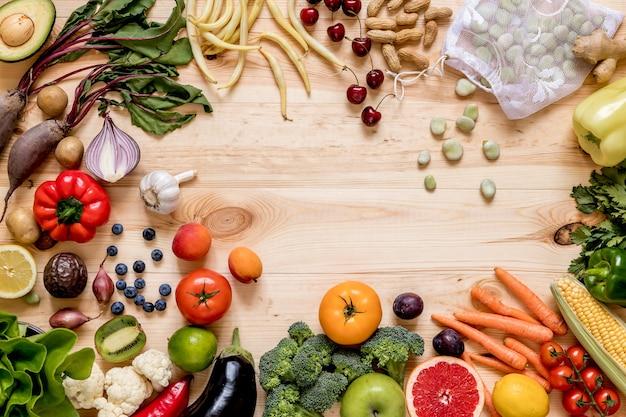 台所の木のテーブルに新鮮で健康的な野菜と果物の現代的な構成。ベジタリアン ビーガンの背景。廃棄物ゼロ。上面図。スペースをコピーします。