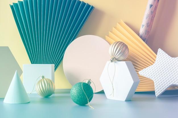 Современная композиция из геометрических фигур шестиугольников и кругов, бумажных вееров на фиолетовом и желтом фоне, вид спереди с рождественскими шарами и подарочной бумагой