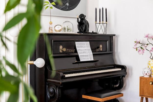 スタイリッシュな黒のピアノ、デザイン家具、植物、装飾、花、モックアップの痛み、トレンディな家の装飾のエレガントなパーソナルアクセサリーを備えた家のインテリアのモダンな構成。