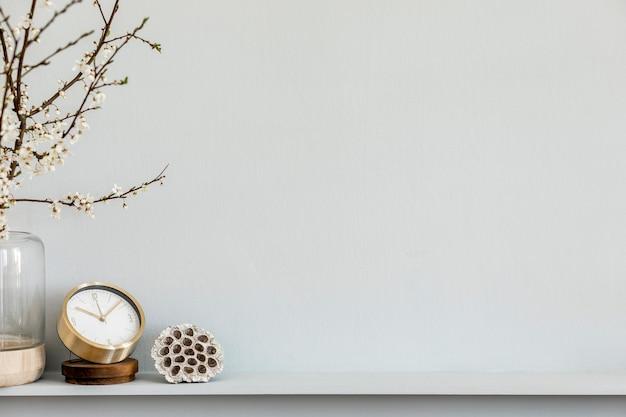 Современная композиция на полке с сухоцветом в дизайнерской вазе, золотые часы, аксессуары и украшения. серая стена. скопируйте пространство.
