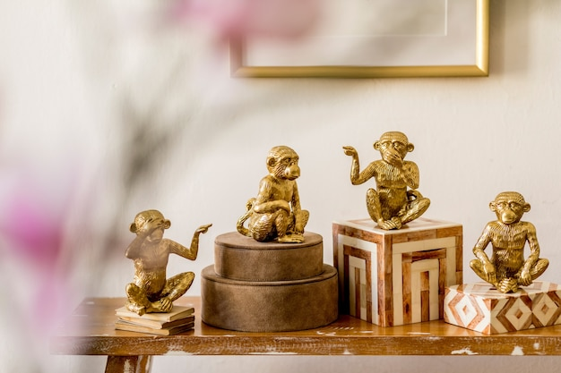Modern composition of stylish accessories, decoration, flowers, gold monkey on the wooden bench at white living room interior. close up. detalis.