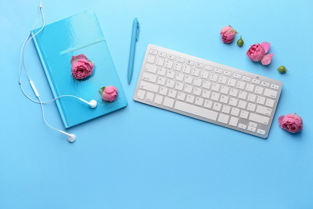 Современная компьютерная клавиатура с канцелярскими принадлежностями и наушниками в цвете