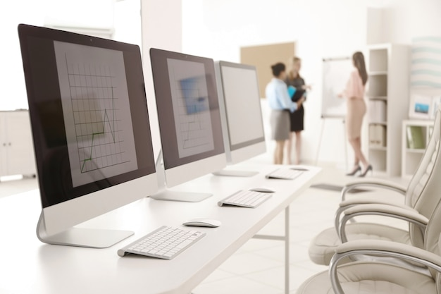 Современные компьютеры и деловые женщины на встрече