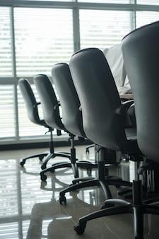 Современные компьютеры, мониторы с двумя экранами и черные стулья.