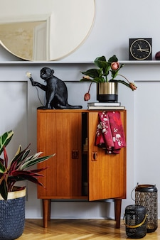 Modern concept of home staging with design wooden commode, round mirror, shelf, clock, plant, rattan decor, book, lanterns and elegant personal accessories at stylish living room.