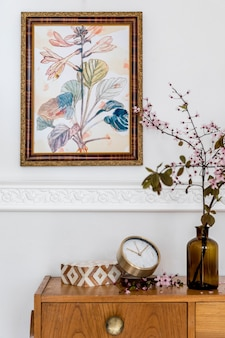 Modern concept of home staging with wall frame, design wooden commode, spring flowers, gold clock and elegant accessories at stylish living room interior.