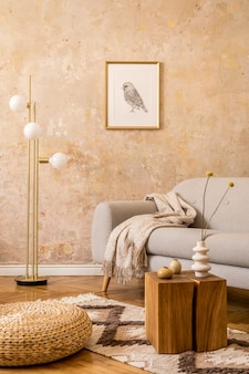 Modern concept of living room interior with gold lamp, design grey sofa, rattan pouf, mock up picture frame, dried flower.