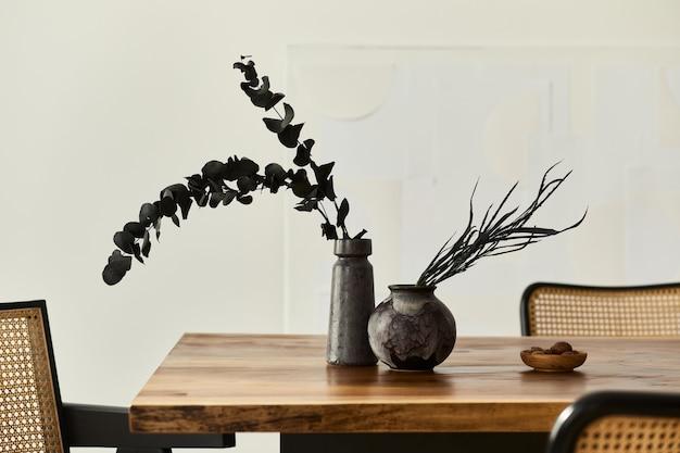 Современная концепция интерьера столовой с деревянным столом, стульями, тарелкой с орехами и сухоцветами в вазах. белая стена .. детали.