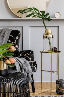 デザインアームチェア、丸い鏡、黒い籐のコーヒーテーブル、花瓶のトロピカルリーフ、装飾、スタイリッシュなリビングルームのエレガントなパーソナルアクセサリーを備えたホームステージングのモダンなコンセプト。