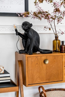 Современная концепция домашней постановки с дизайнерской черной лампой, деревянным комодом, весенними цветами, книгой, корзиной и элегантными аксессуарами в стильном интерьере гостиной.
