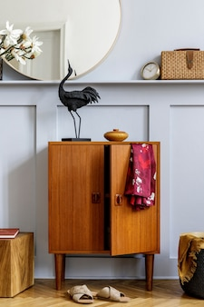 세련된 거실에서 디자인 나무 옷장, 둥근 거울, 선반, 시계, 식물, 큐브, 옷, 책, 등나무 가방 및 우아한 개인 액세서리로 홈 스테이징의 현대 개념.