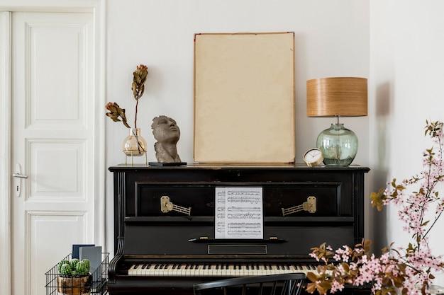 デザインの黒いピアノ、テーブルランプ、金の時計、花瓶のドライフラワー、スタイリッシュな家の装飾のエレガントなパーソナルアクセサリーを備えたモックアップポスターフレームのモダンなコンセプト。