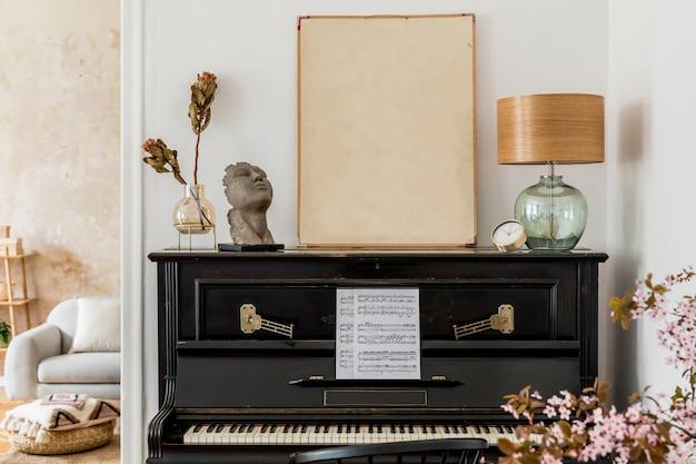 Современная концепция рамки для плаката с дизайнерским черным пианино, лампой, золотыми часами, засушенными цветами и элегантными личными аксессуарами в стильном домашнем декоре.