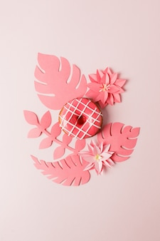 Modern concept pastry - pink glazed donut and origami papercraft flowers and plants on pink