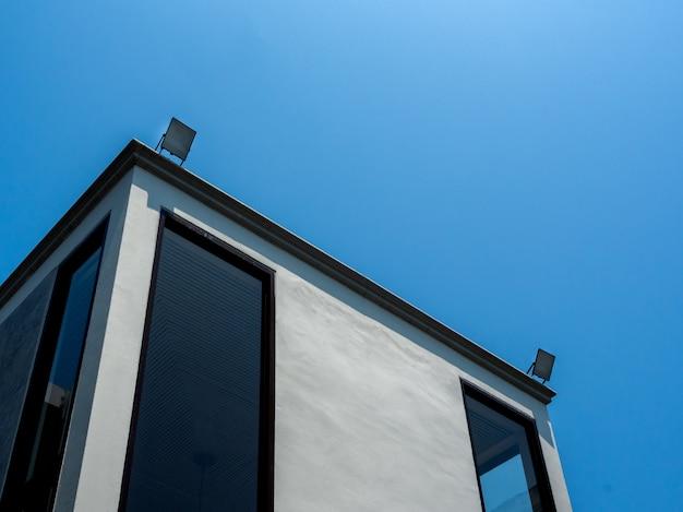 青い空の上にledフラッドライトを備えたモダンなコンクリートの建物