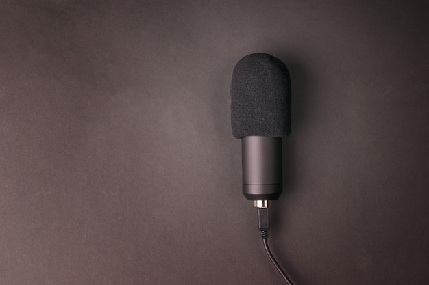 Modern condenser microphone on a black surface