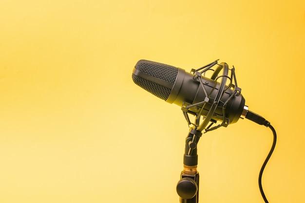 Современный конденсаторный микрофон на подставке на желтой стене