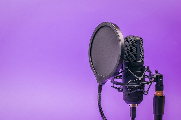 Modern condenser microphone on stand on purple. sound recording equipment.
